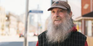 elderly homeless man looking optimistic