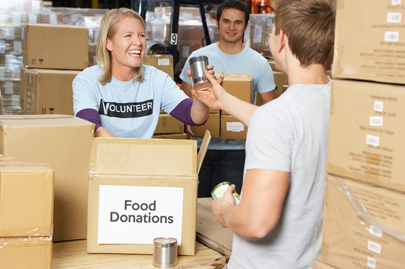 Group Of Volunteers Collecting Food Donations In Warehouse